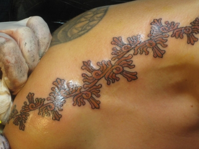 Getting my Mayan sun ray tattoo across the tops of my shoulders, by Walt Clark in 2010, for my 50th birthday