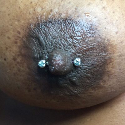 Female nipple piercing with ball-set gem barbell clear stones