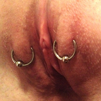 Outer labia piercings placed fairly high, near the clitoris, a pair on each side with captive bead rings