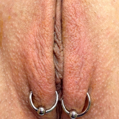 A pair of outer labia piercings placed low on the lips with captive bead rings