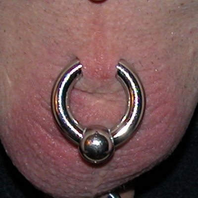A stretched scrotum piercing with large gauge captive ring